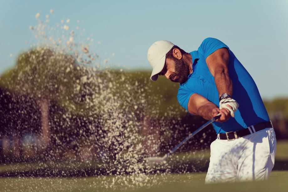 Golfer hitting the ball out of a sand trap.