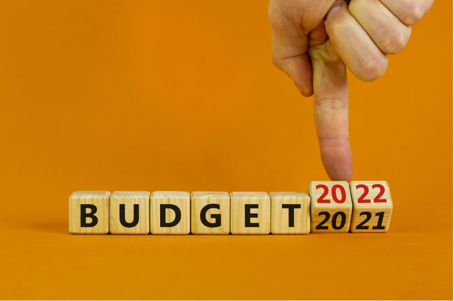 """Finger pointing to the year on wooden blocks that spell out """"budget"""""""