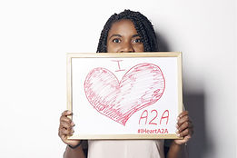 Woman holding an I Heart A2A sign.