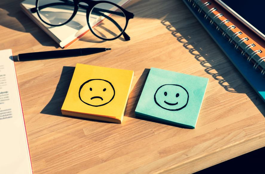 Emotional Intelligence: Post-It Notes with a happy and sad face with objects on a desk.