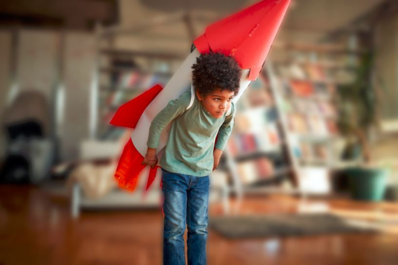 Boy holds a homemade rocket toy on his back with great difficulty.