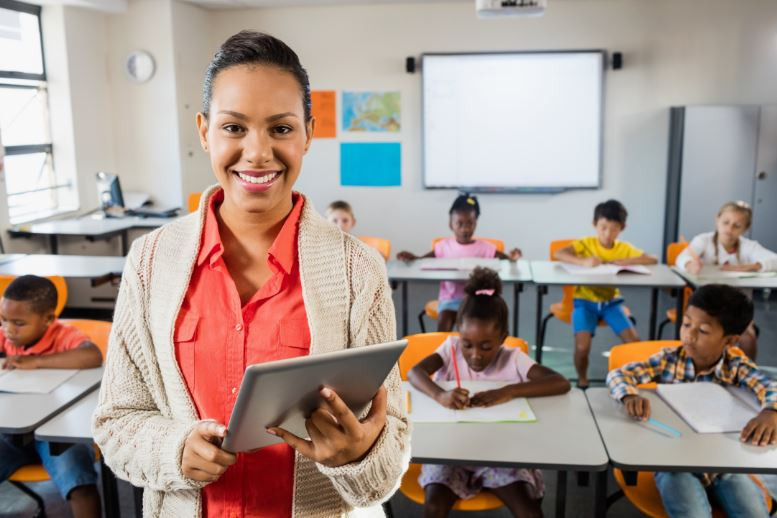 Teacher with a tablet standing in front of a classroom full of students at their desks.