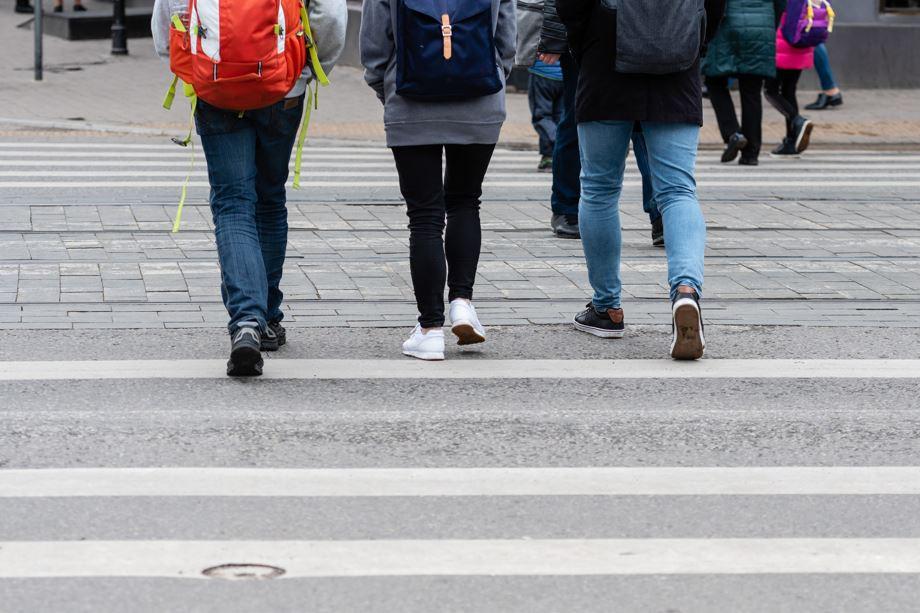Shoes and legs of people wearing backpacks walking away in a crosswalk.