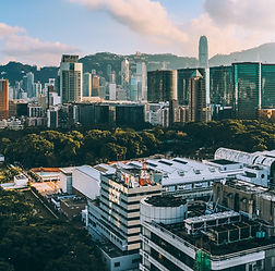 Skyline view of Hong Kong city center. Green, misty hills in the background.