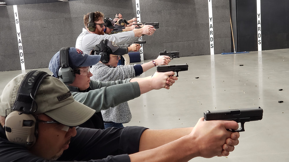 people shooting pistols indoors
