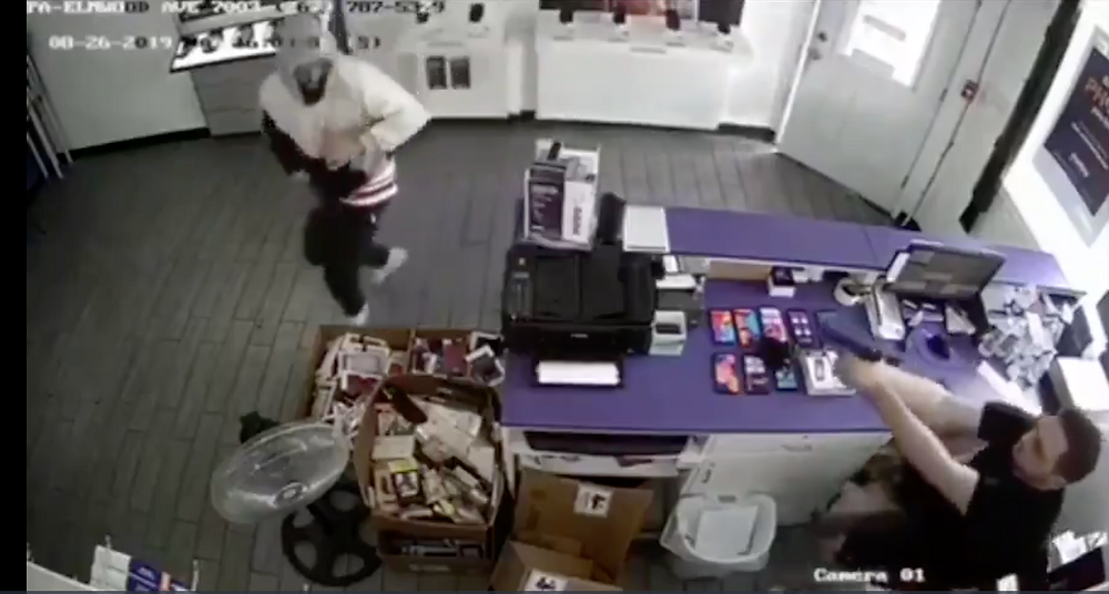 This employee at a cell phone store reacts quickly to an armed robber and effectively responds from a seated position.