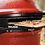 Pizza being inserted into DoJoe in red Kamado Joe grill