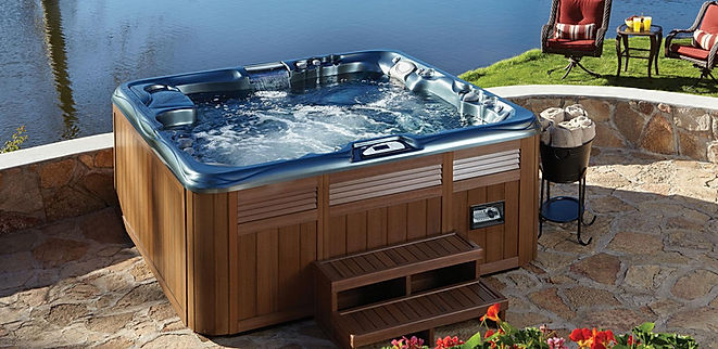 blue and brown square hot tub on stone patio infront of water and grass