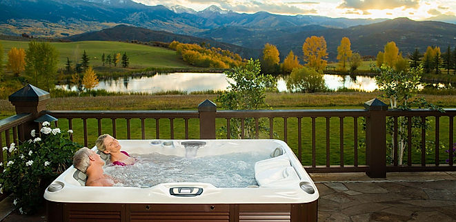 one man and one woman relaxing in square white and brown hot tub in grassy mountain valley