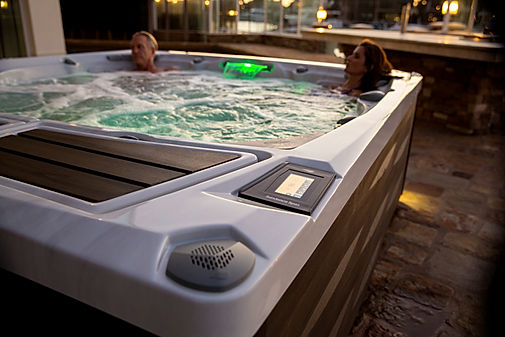 one man and one woman relaxing in white marble hot tub with green lights