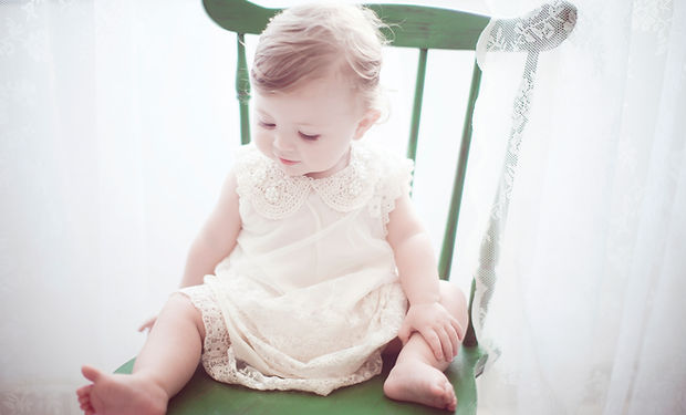 A happy looking young child sitting on a wooden green chair