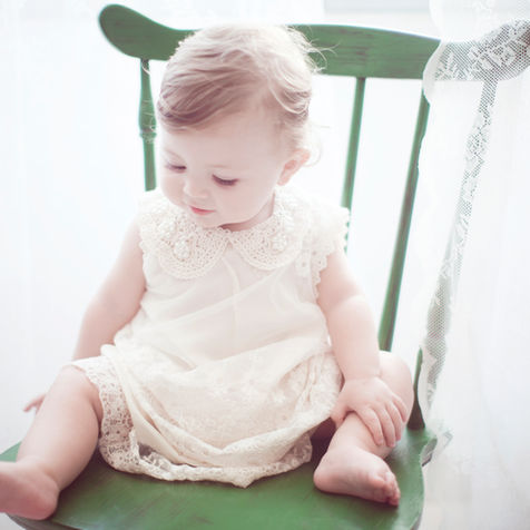Top photographers: baby girl sitting on green chair celebrating first birthday party.