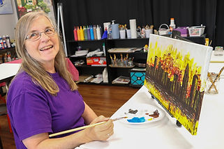 Owner and artist, Mary paints the skyline of Charlotte, N.C.