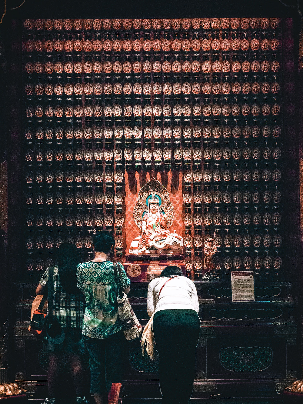 An older woman and 2 younger women praying to the Buddha statue