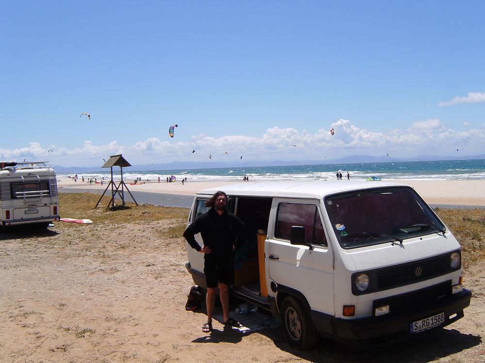 Auto am Strand von Spanien, mit Surfern im Hintergrund