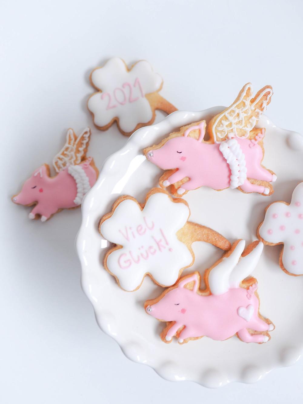 Kekse in Form von fliegenden Schweinchen und Kleeblättern, verziert mit Royal Icing. Die Flügel sind mit Embrodery Technik gespritzt und die Nase mit einer silbernen Zuckerperle besetzt.