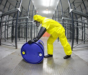 person-in-yellow-suit-rolling-blue-barrel.jpg