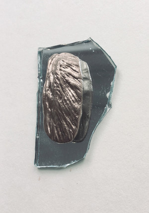 Deze vorm is geïnspireerd op de (wal)noot, en is gemaakt van koud porselein met goudverf, gelegd op een stukje spiegel. Hij is circa 3 x 4 cm. Het is een terugkerend kenmerk van mijn werk dat alles bestaat uit losse delen die bij elkaar gelegd worden. De objecten kunnen op die manier telkens worden samengesteld tot nieuwe beelden, als een soort lego.