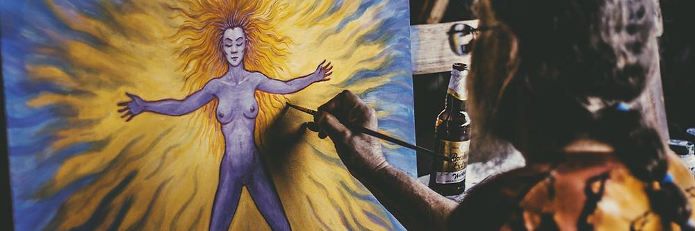 Homem de óculos, cabelos longos, pintando um quadro.