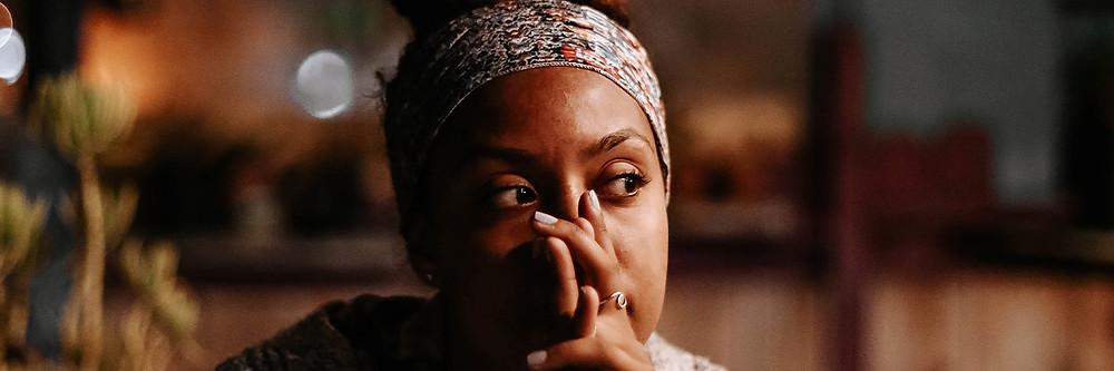 Mulher com lenço na cabeça, mãos cobrindo boca e nariz, olhando para o lado.