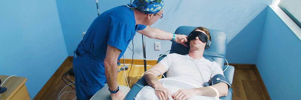 Sessão de administração intravenosa de ketamina: Um homem está deitado em uma poltrona, os olhos estão cobertos com uma máscara, e ele está acompanhado de um médico todo vestido de azul.
