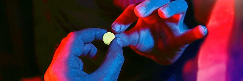Duas mãos de pessoas diferentes, uma passando um comprimido de MDMA para outra.