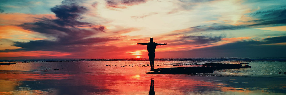 Pessoa em pé na praia, com braços abertos, durante o pôr do sol.