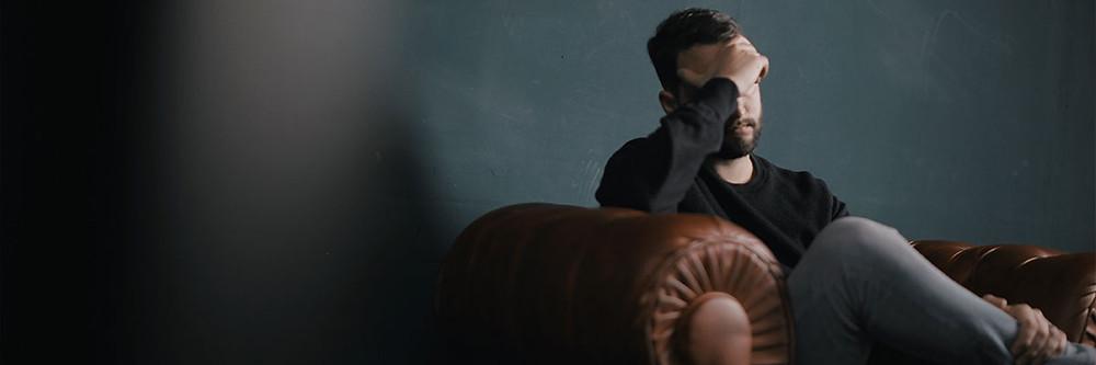 Homem sentado em um sofá, com a mão na testa, aparentando estar depressivo.