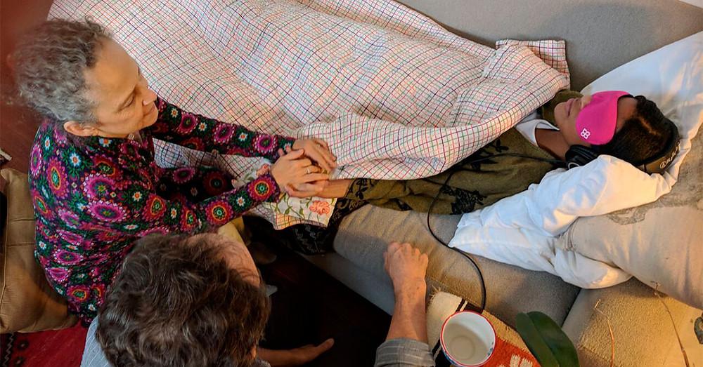 Mulher em terapia com MDMA, acompanhada por dois terapeutas. Um homem e uma mulher.