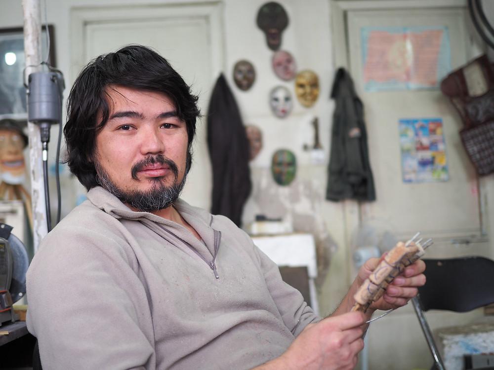 Bishkek Artist Dzhum sitting in his workshop
