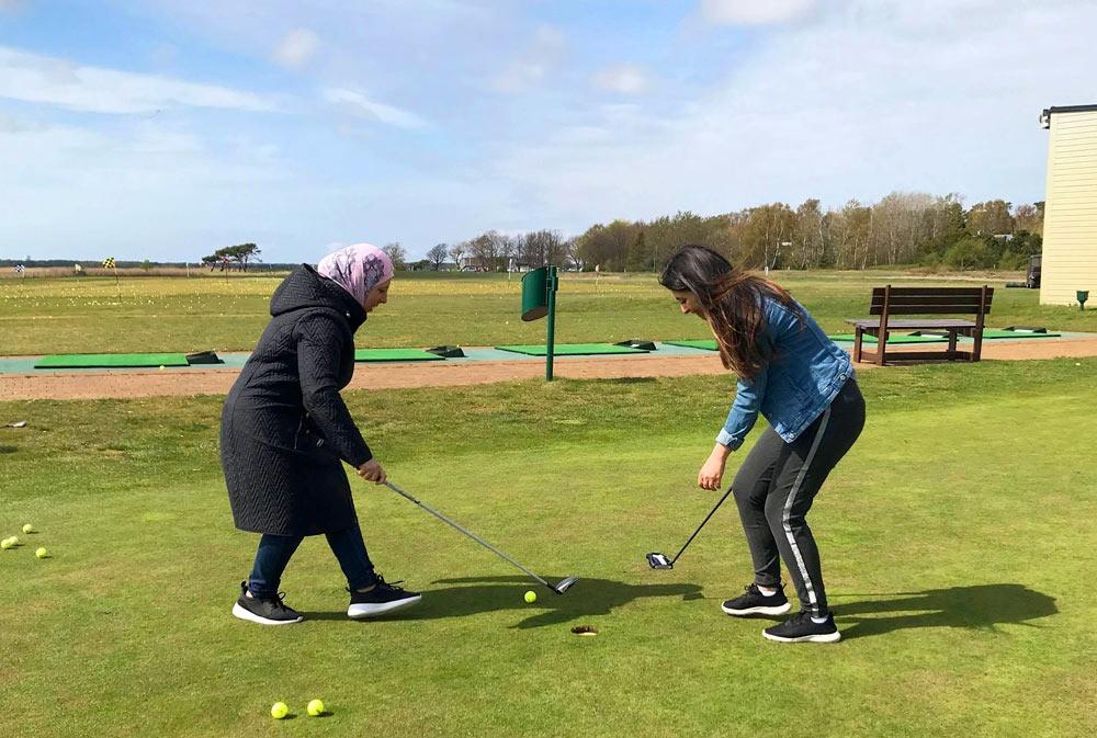 Mor och dotter från Syrien provar på golf på Ljunghusens golfklubb i projektet Golf för nya vänner.