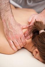 Ostéopathe massothérapeute réduisant tensions aux trapèzes et à la nuque femme