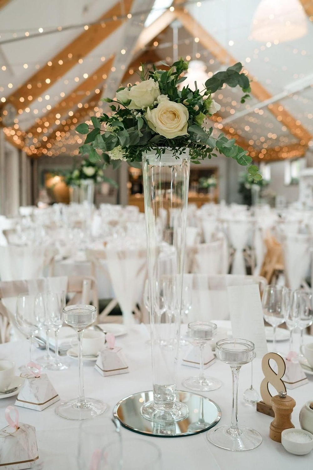 Floral centrepieces designed in glass vases for this wedding