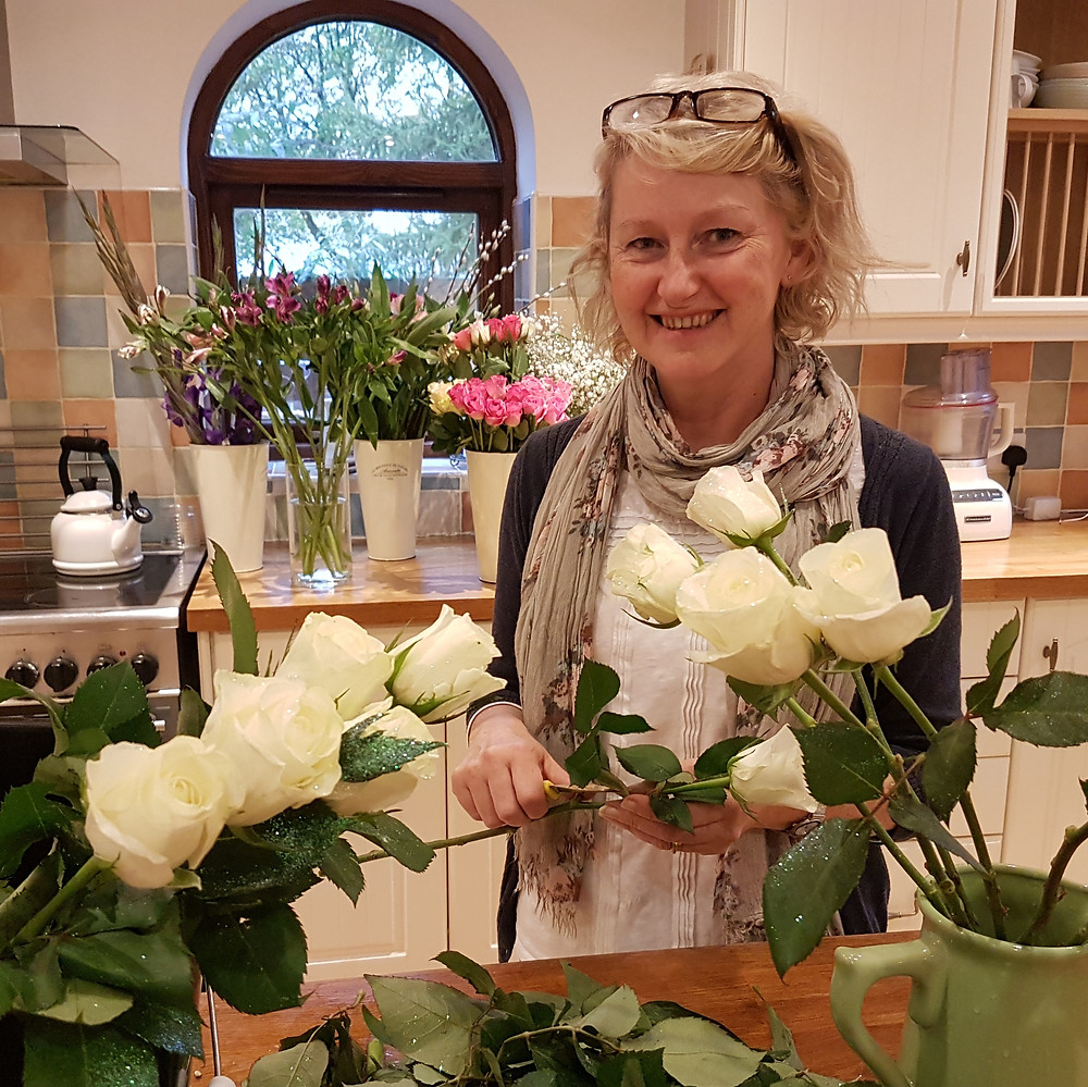 Julie in her farmhouse kitchen in Lincoln, surrounded by beautiful blooms