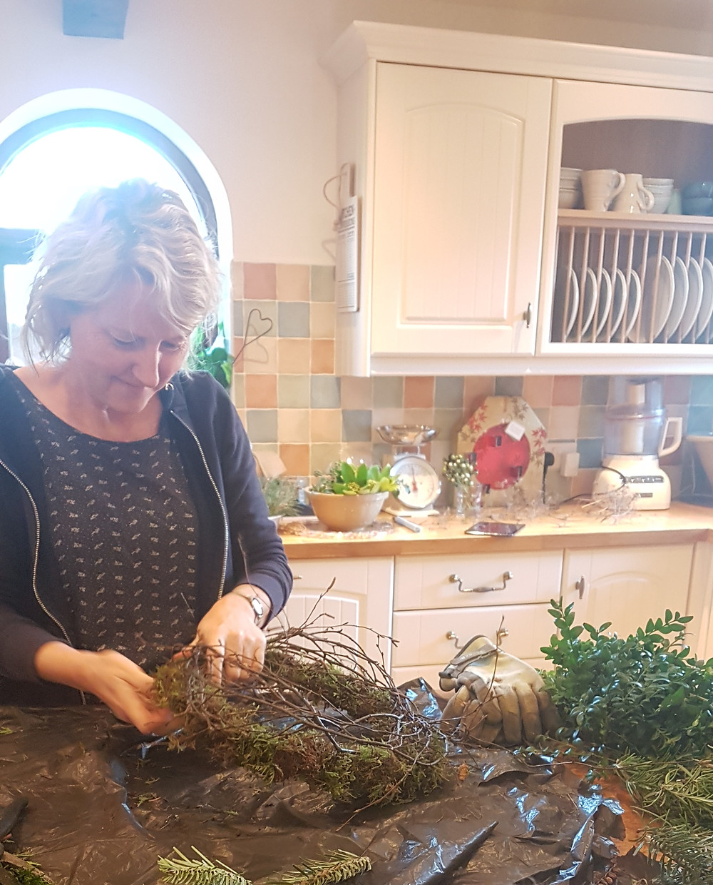 Julie surrounded by foliage collected from our cutting garden and the breathtaking farmland and countryside where she lives. This was the start of wreath-making season in 2017. So much fun!