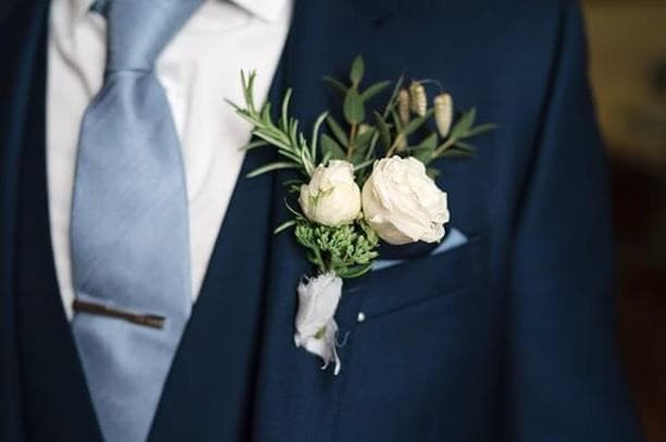 A classic buttonhole styled as a mini bouquet with spray roses and greenery