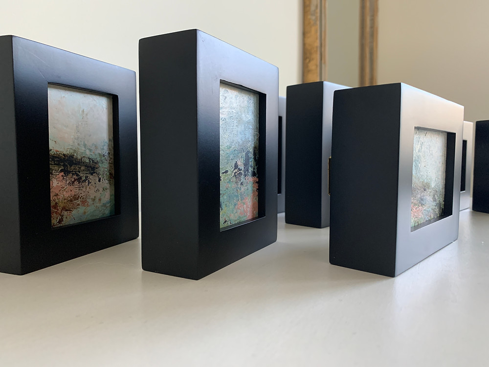 "a series of small paintings that are 2.5"" x 3.5"" and framed in black wood frames"