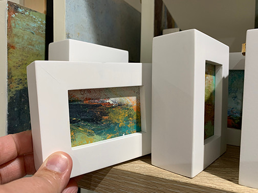 """a series of 2"""" x 3"""" paintings in white wood frames"""