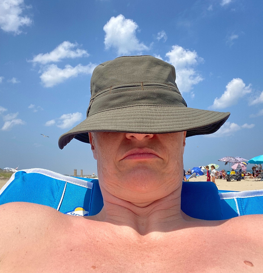 the author is reclined in a beach chair on a sunny day at the beach with their fishing hat pulled down over their eyes.