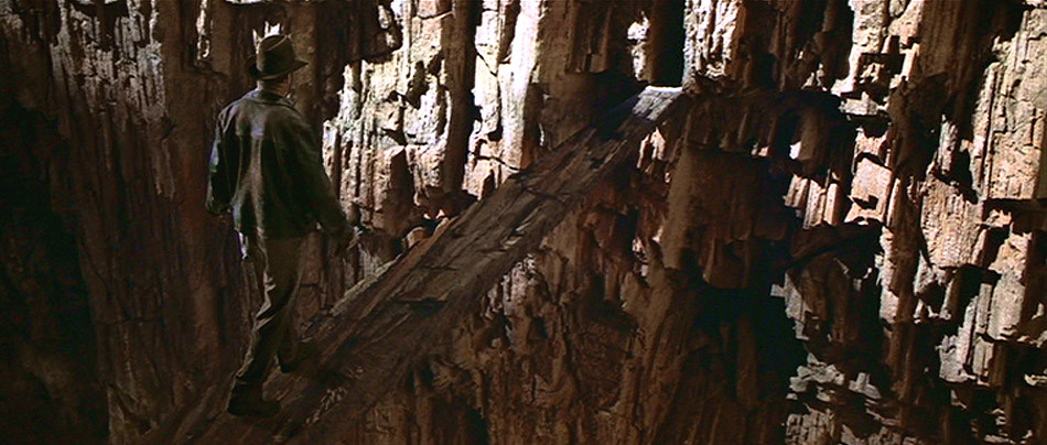 Indiana Jones walks tentatively across a seemingly imaginary stone bridge between two walls of stone