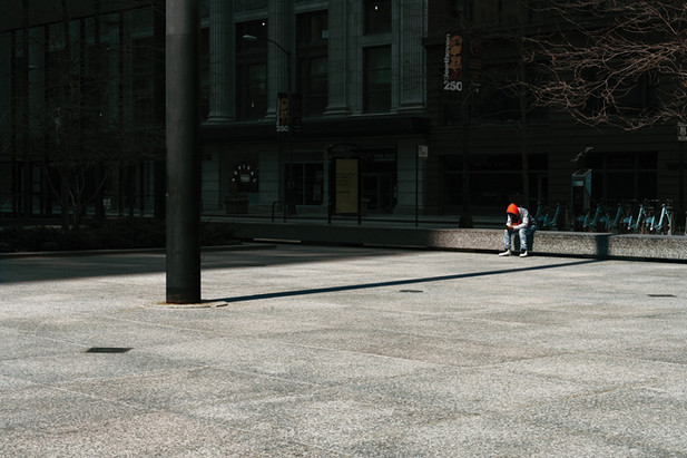 Unidentified man sits in empty Federal Plaza in downtown Chicago during rush hour on April 3, 2020.