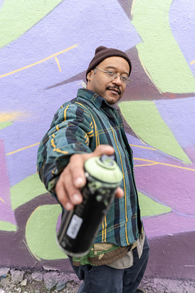 """Darrell """"Artistic"""" Roberts of Chi-ROCK Nation in front of his mural at the Logan Square permission wall (2934 W. Medill, near Milwaukee and Fullerton) on Oct. 26, 2019. For the Chicago Reader."""