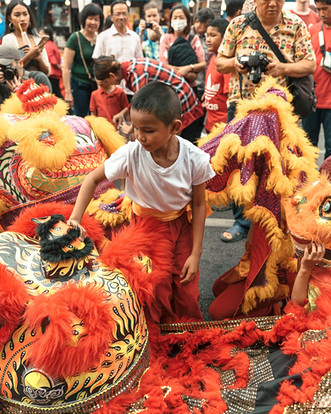Crowds celebrate Chinese New Year in Bangkok, Thailand just weeks before the the city shuts down for the COVID-19 pandemic. Unidentified child takes his costume off at the Chinatown celebration on January 25, 2020.