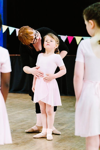 Miss Amy gives one ballerina individual feedback in a primary ballet class at Theative in Streatham