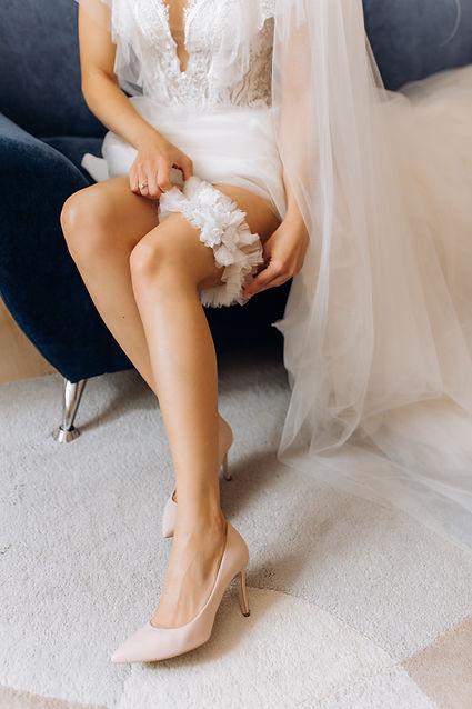 bride-is-wearing-wedding-garter-her-leg-sitting-armchair.jpg