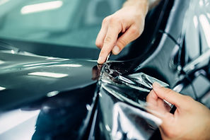 Worker hands installs car paint protecti