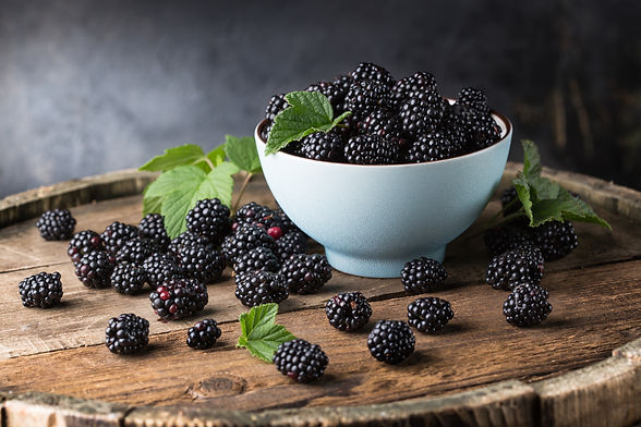 Ripe blackberries with leaves in a bowl on a wooden board on a dark background.jpg