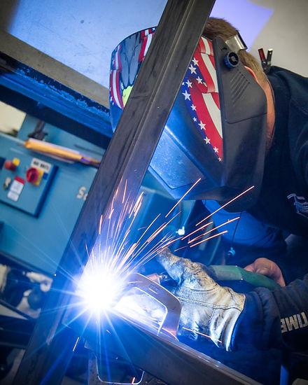 Welder wearing helmet using welding tools