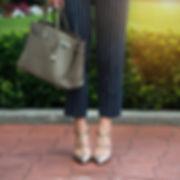 Women's legs in grey high heels shoes. G