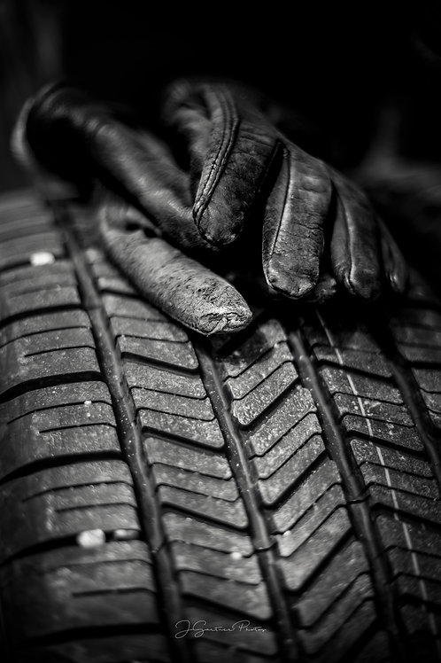 Black and white image of a pair of gloves resting atop a summer tire